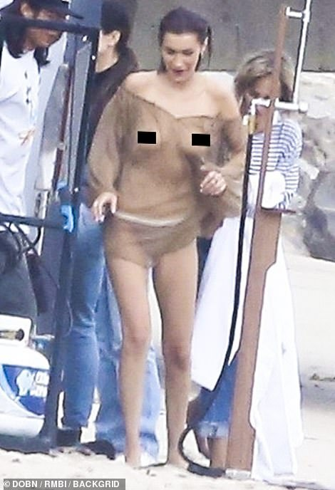 Bella Hadid leaves little to the imagination in a sheer blouse and bikini bottoms in Malibu