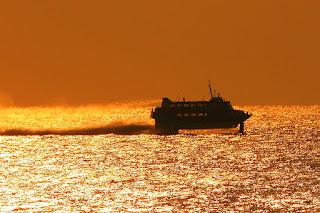夕焼けで赤く染まった空と海の上を走るジェット船のシルエット