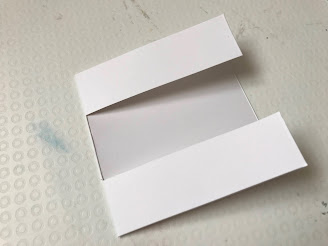 Front of a white square card slightly open with a middle section cut out across the card