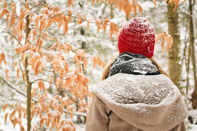 Tyttö kävelee luonnossa ja katsoo lumisia puita