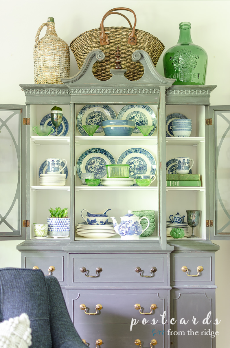 blue willow dishes and green depression glass in painted china cabinet