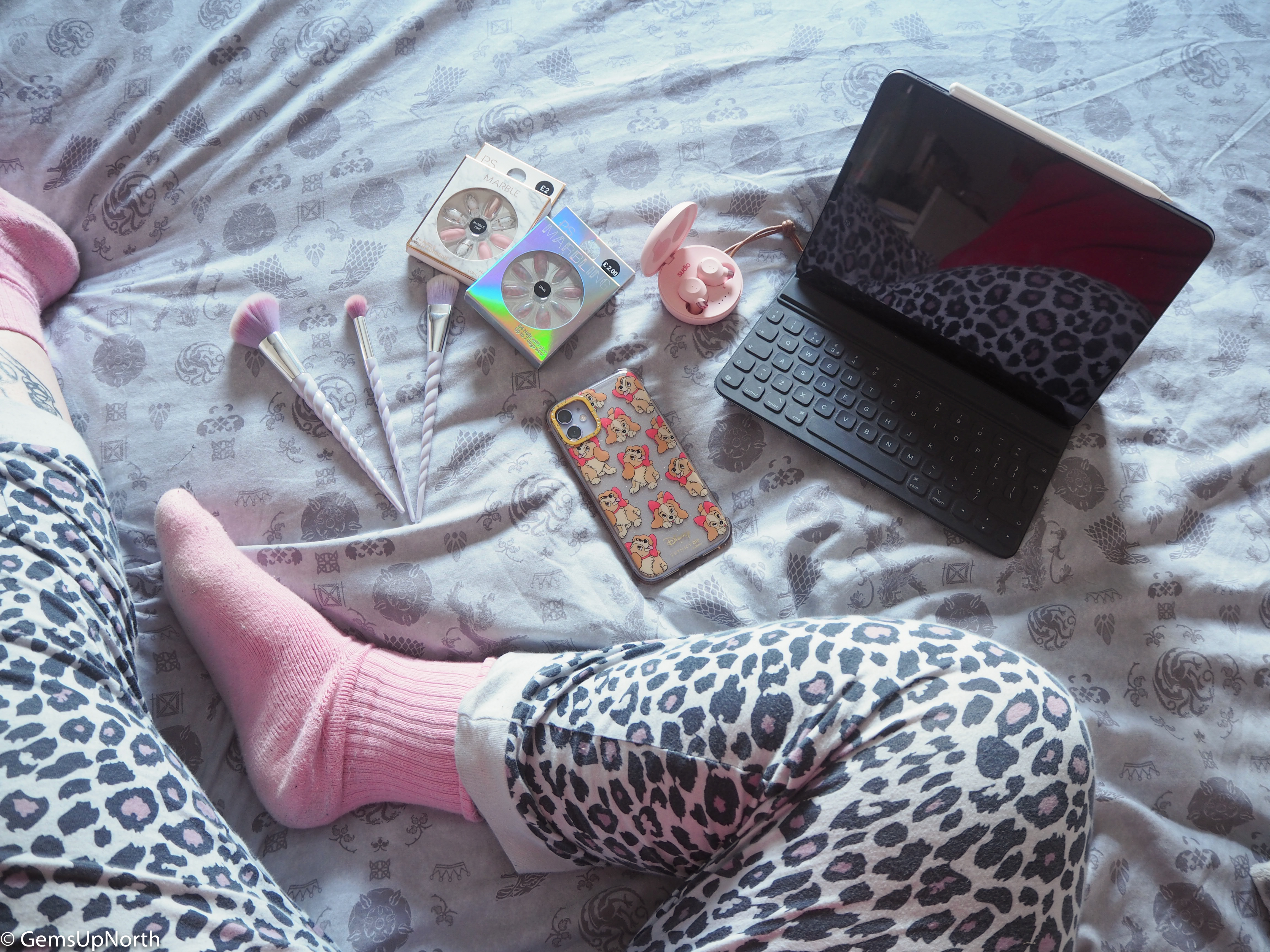 Shot of GemsUpNorth's leg with leopard print PJs on, FEM Sudio ear buds, iPad, Phone and some beauty bits on a GOT bed set