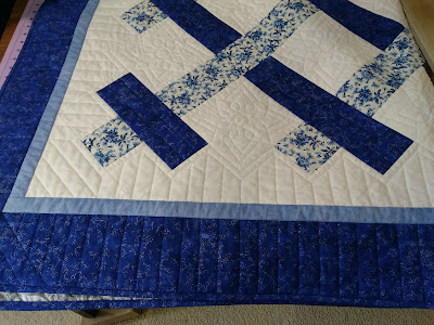 Paino key quilting motif in borders of blue and white patchwork quilt