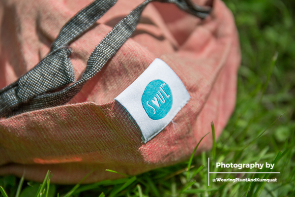 [Image of a dusty peach linen onbuhimo with black chambray hood straps and a blue SOUL logo on the carrier's hood visible on green grass in sunlight.]