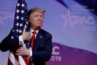 President Trump hugs the U.S. flag