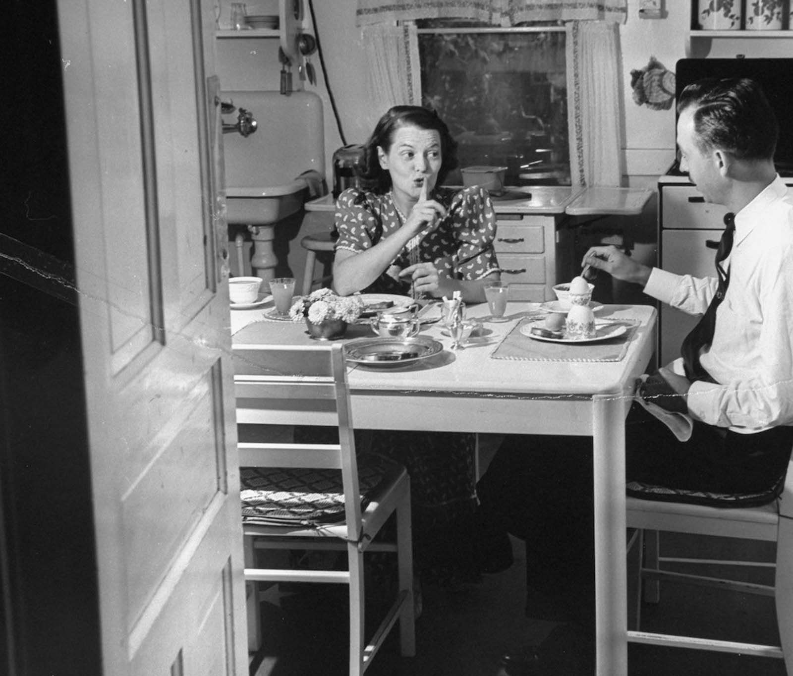 Jane shushing her husband Gilbert, as they sit having a quiet 6:30 a.m. breakfast before their three kids wake up, in the kitchen at their home.