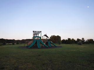 a green and brown play structure with 7 green plastic slides at Siouxland Freedom Park in South Sioux City, Nebraska