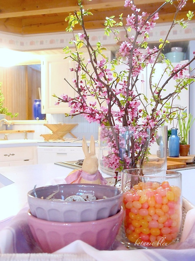 Beautiful Spring Centerpiece with redbud branches, pastel jelly beans, purple bowls, bird eggs, and iron bunny in a white basket