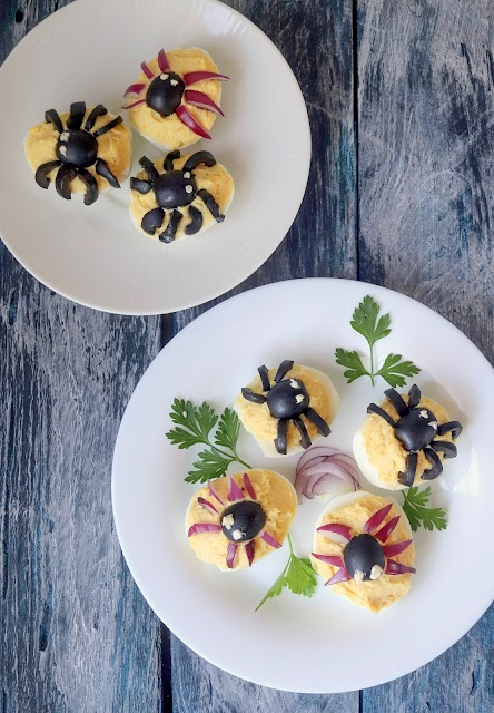 spider deviled eggs on a plate with a herb garnish.