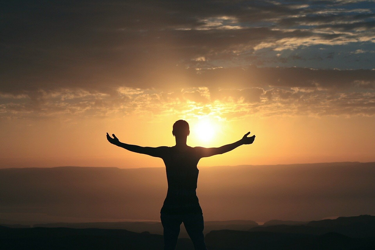 the silhouette of a man with outstretched arms looks at the rising sun for a blog post about movies to be thankful for
