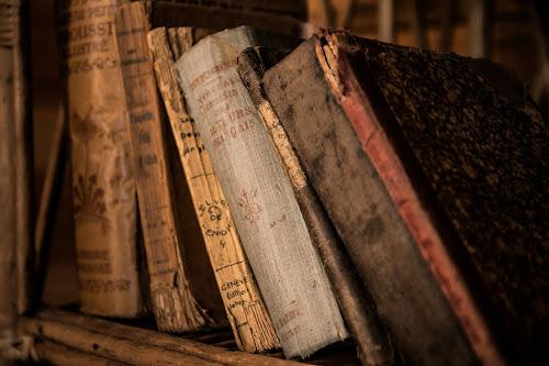 Livros velhos e antigos mal arrumados em uma estante de madeira
