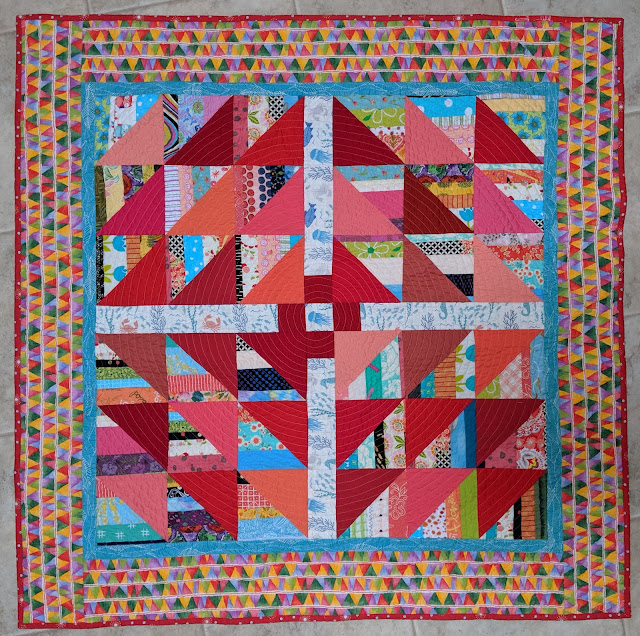 HSTs of strings pair with red, orange, and pink solid triangles to form The Square Deal block in the center of this quilt. It is surrounded by a narrow turquoise inner border and a wider print of colorful triangles.