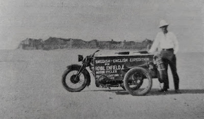 Man stands next to motorcycle in desert.