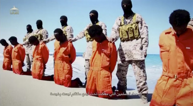 Image Attribute: Islamic State militants stand behind what are said to be Ethiopian Christians along a beach in Wilayat Barqa, in this still image from an undated video made available on a social media website on April 19, 2015. REUTERS/Social Media Website via Reuters TV/File Photo