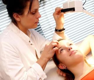 Foto de una dermatóloga revisando la piel de su paciente