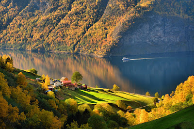 A house by a green field on a fjord with colorful forests all around it. There is a boat moving on the water.