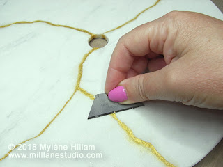 Scrape away any clay overfill with a sharp blade.