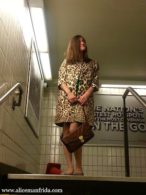 A woman in a leopard print coat carrying a brown hand bag looks to the side while standing at the top of the stairs in a subway station.