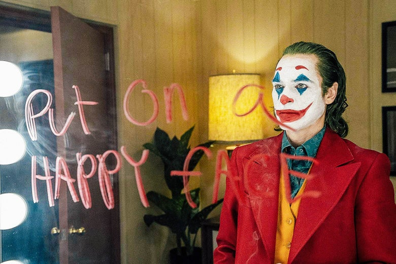Joker writing put on a happy face on a mirror