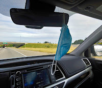 Face mask hanging from the rear view mirror of a vehicle driving on the freeway
