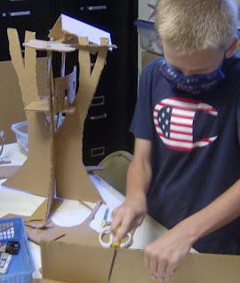 Using shears to cut a cardboard shape