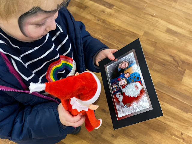 Overhead shot of a girl with an elf toy from Santa looking at a photo of her with Father Christmas