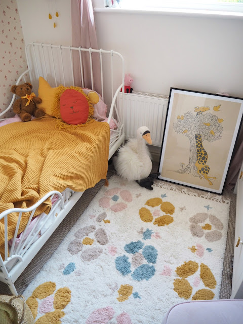 A pink and mustard yellow girls nursery bedroom, complete with cute accessories, colourful decor and homemade DIY touches. Including the IKEA Minnen bed, boho wall hanging, and IKEA hack dollhouse. Nursery inspiration and budget ideas.