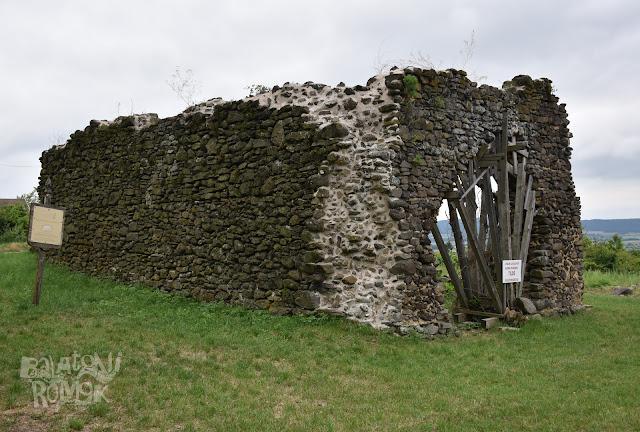 Töttöskál templomának romja, a hosszanti, ablak nélküli, magasan álló északi fal, és a nyugati oldalon lévő, fával aládúcolt kapunyílás van a képen.
