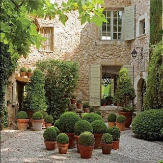 Garden design ideas with terracotta pots with boxwood and stone walls and shutters