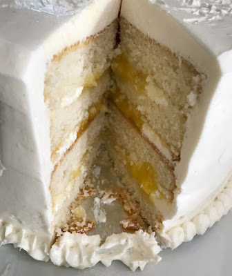 four layers of white cake with white frosting and lemon curd filling in a stacked cake with a piece missing to reveal the middle