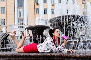 Девушка в розовом у фонтана пьёт сок