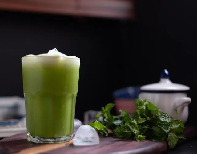 Vaso de cristal transparente con jugo verde, sobre una mesa de madera con hojas de menta y una jarra de cerámica de color blanco