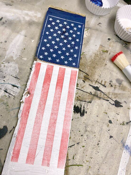 Stenciled red, white and blue flag on a wooden stake