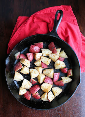 potato chunks tossed with oil and seasonings in cast iron skillet, ready to roast