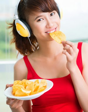 Girl with headphones eating crisps
