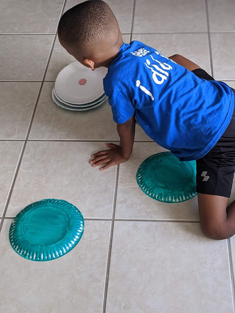 African-American boy playing in the kitchen on the floor