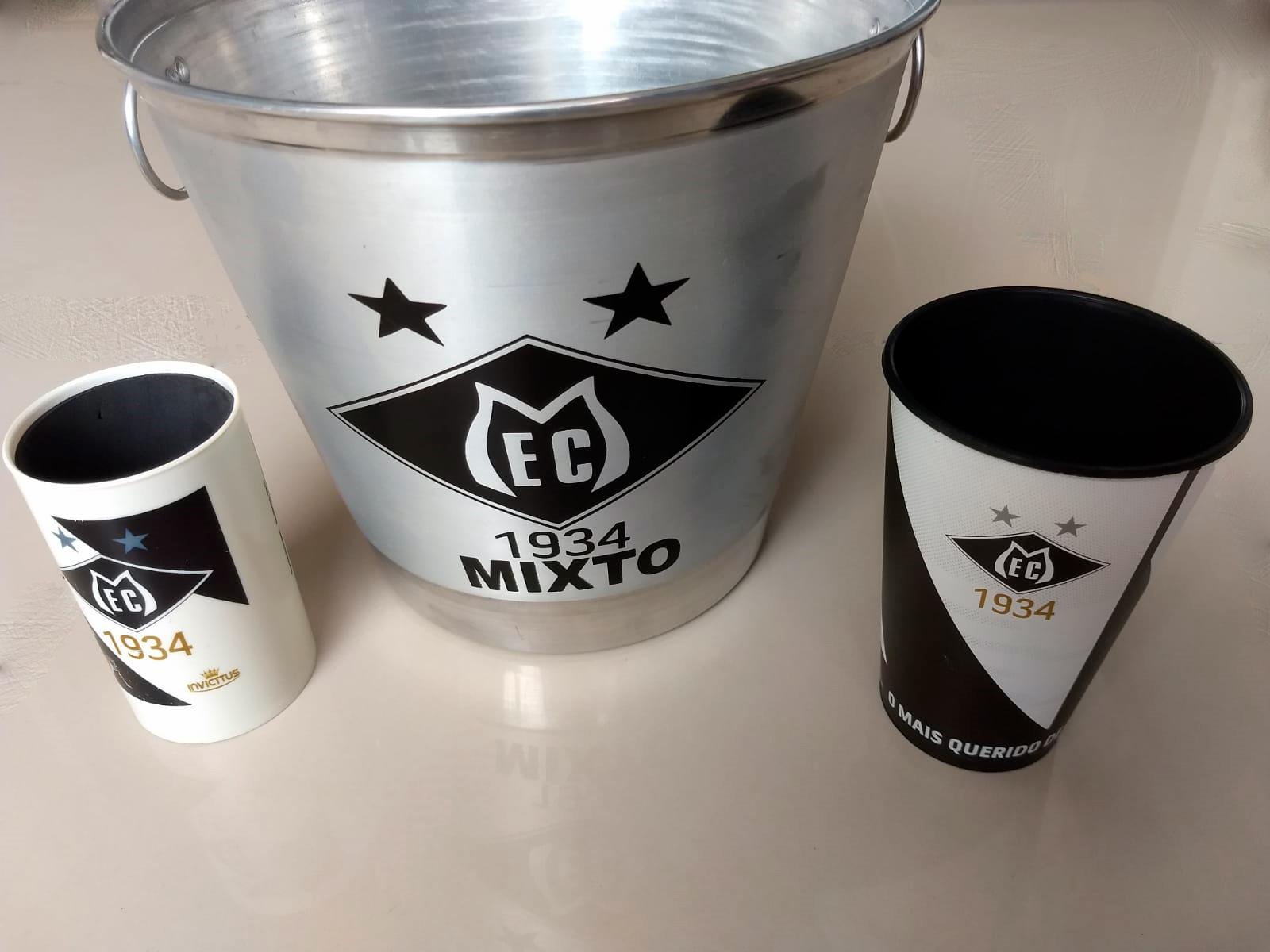 Na foto um porta lata branco do Mixto, um balde de metal inox para gelo eu copo plástico preto, produtos oficiais