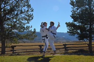 Two adult black belts practicing kicking through perseverance