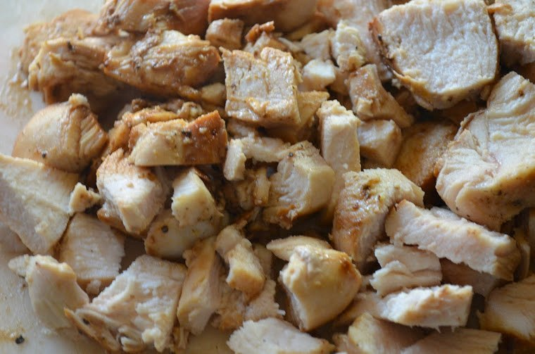 Chopped Cooked Chicken on a white cutting board.