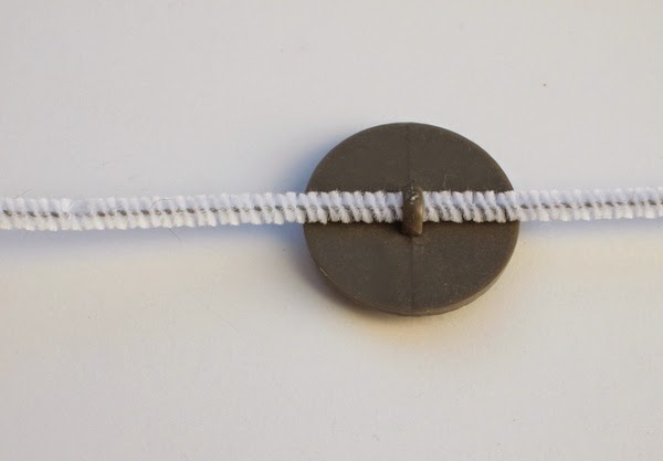 string pipe cleaner through back of button to make DIY kids jewlery