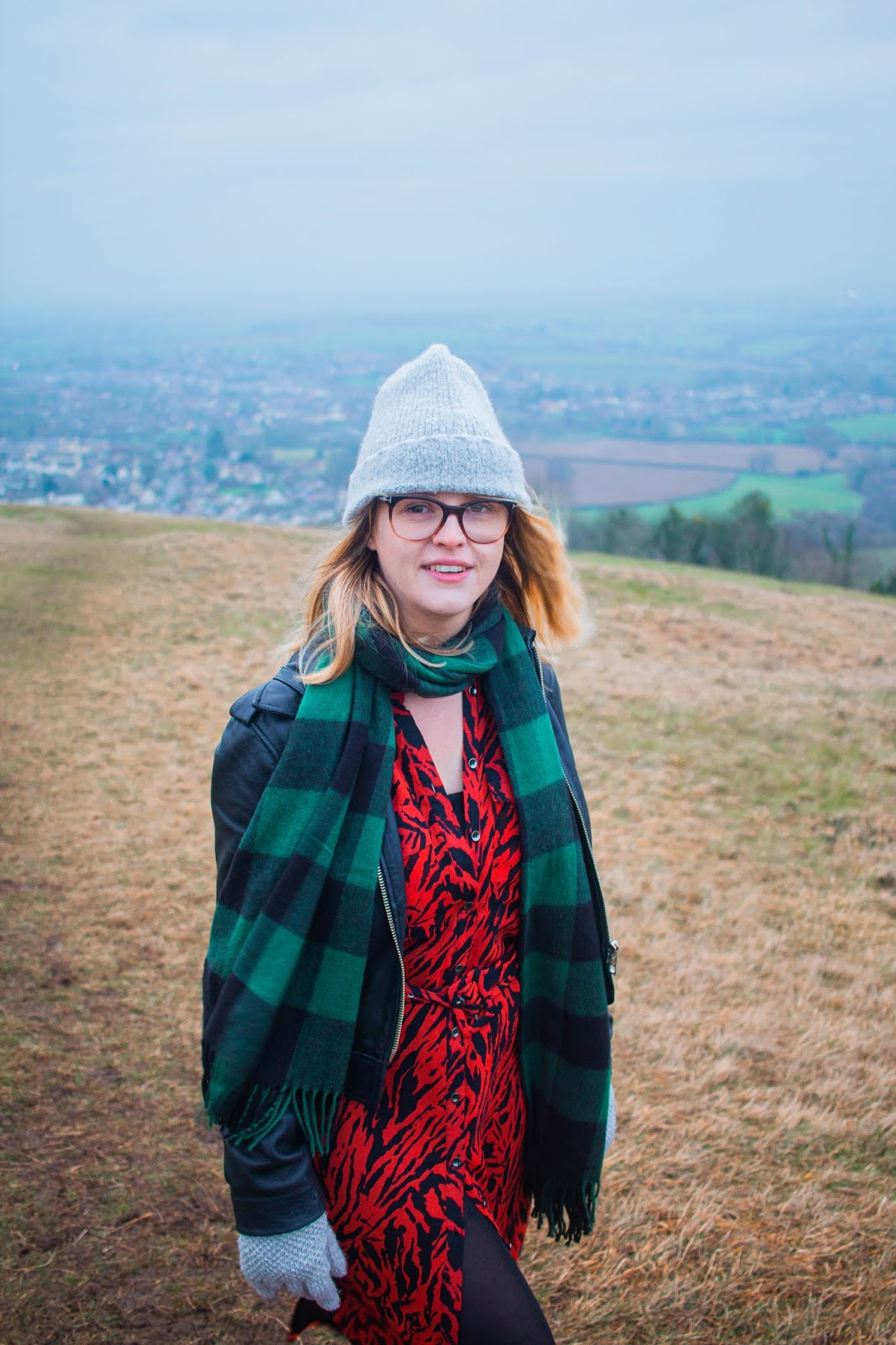 chloe harriets on walk in nature, scenic view, wearing mint velvet dress, whistle leatther jacket and beanie. 2020 bucket list