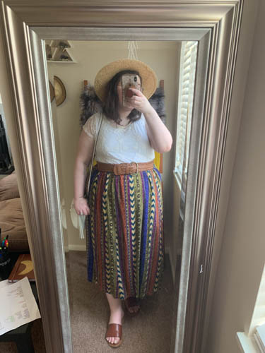 A mirror selfie of an outfit of a straw sunhat, white lace blouse, patterned maxi skirt and brown faux leaher slide sandals.