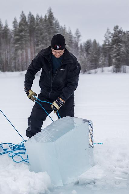 Mies hinaa avannosta valtavaa jääkuutiota