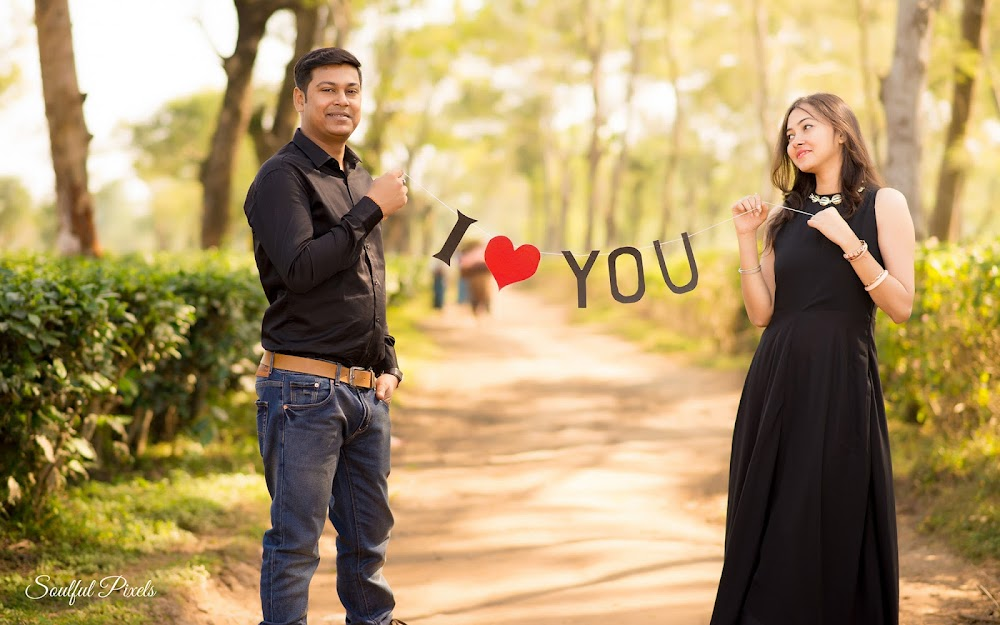 Couple In Black Dress Holding I Love You Sign