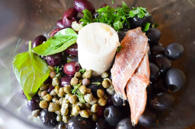 Food Processor with Black Olives, Kalamata Olives, Anchovy Filets, Garlic, Capers, Olive Oil, Lemon Juice, Parsley, Thyme Leaves, Basil Leaves for Black Olive Tapenade from Serena Bakes Simply From Scratch.