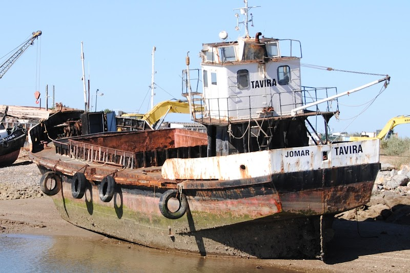 Rusted fishing boat on a river bank