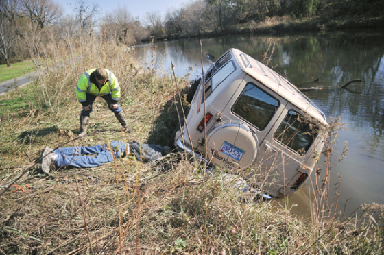 Two men try to save van on edge of river bank, partially in water