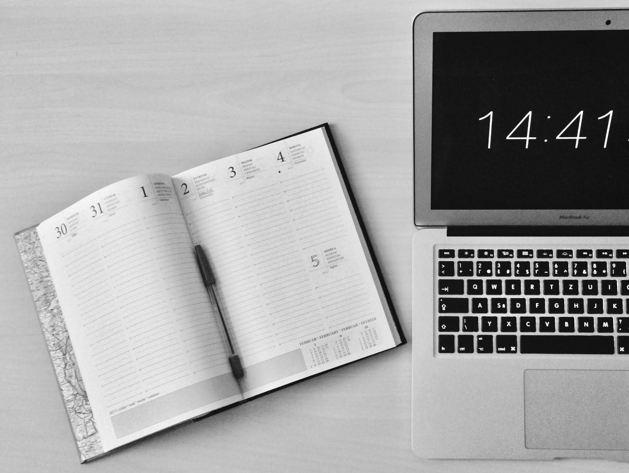 flat lay photograph of notebook and macbook next to each other
