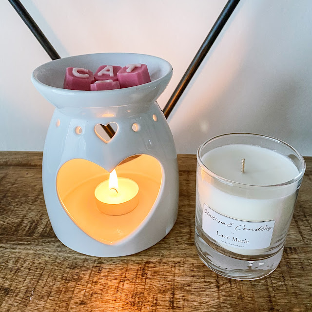 Wax melter with wax melts on top and a classic candle in a glass jar