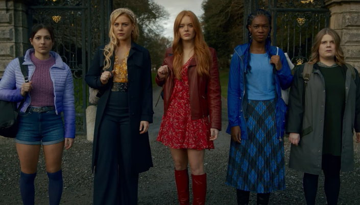 Cinco mulheres na frente de um portão grande e atrás dele tem uma floresta. Elas estão enfileiradas olhando para frente e todas seguram mochilas. Da esquerda para direita, a primeira é branca, tem cabelo preto e usa um casaco azul e um short jeans. Ao lado dela está uma mulher mais alta, loira branca que usa um sobretudo preto e uma calça jeans e uma camiseta amarela. No meio tem uma uma mulher ruiva branca com um vestido vermelho, um casaco de couro vermelho e botas de cano alto vermelho. Ao lado dela tem uma mulher negra com um vestido azul escuro e um cardigan azul escuro, ela tem cabelo com tranças. Ao lado dela tem uma mulher mais baixa e gorda com casaco cinza e uma calça e blusa verde escuro, ela é loira e branca.